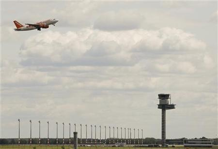 An aircraft operated by easyJet passes the tower of future Berlin Brandenburg international airport Willy Brandt (BER) in Schoenefeld, May 17, 2012. The opening day of the capital's long-awaited new airport replacing Tegel and Schoenefeld has been pushed back by almost a year to March 17, 2013. REUTERS/Tobias Schwarz (GERMANY - Tags: POLITICS TRANSPORT)