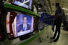 A customer watches televisions in a supermarket in Nice during a live broadcast of France's President Francois Hollande's news conference at the Elysee Palace, November 13, 2012. Hollande, facing plunging poll ratings, defends his first six months in a high-profile news conference. REUTERS/Eric Gaillard (FRANCE - Tags: POLITICS MEDIA BUSINESS)