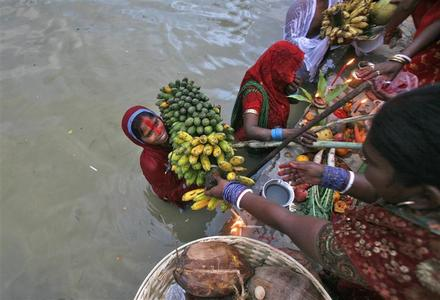 A Hindu devotee holds bananas in the waters of Durga Dari Lake while worshipping the Sun god during the Hindu religious festival ''Chhat Puja'' on the outskirts of Agartala, capital of Tripura November 19, 2012. REUTERS/Jayanta Dey