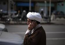 A cleric talks on his mobile phone as he arrives at a religious conference centre in Qom, 120 km (75 miles) south of Tehran, March 10, 2011. REUTERS/Morteza Nikoubazl
