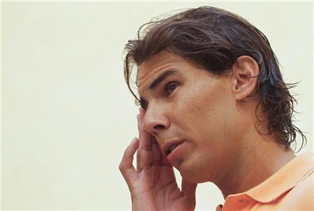 Spain's Rafael Nadal gestures between television interviews, during which he detailed reasons for pulling out of the U.S. Open, in Palma de Mallorca, on the island of Mallorca August 17, 2012. REUTERS/Enrique Calvo