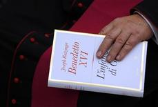 """El papa Benedicto XVI publicó el martes la última parte de su trilogía sobre la vida de Jesús, en la que reafirma con fuerza que el que Jesús naciera de una mujer virgen es una verdad """"inequívoca"""" de la fe. En la imagen, un obispo sostiene una copia del libro de Benedicto XVI """"La infancia de Jesús"""" durante una presentación en el Vaticano, el 20 de noviembre de 2012. REUTERS/Alessandro Bianchi"""
