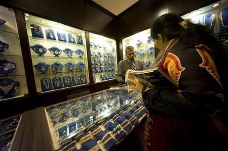 An woman shops at an Indian jewellery stall at the Jewellery Arabia 2012, the biggest jewellery exhibition in Manama, Bahrain, October 18, 2012. REUTERS/Hamad I Mohammed/Files
