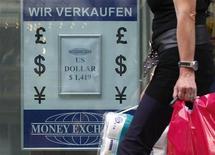 Женщина проходит мимо пункта обмена валют в Вене 19 августа 2011 года. Евро стабилен к доллару во вторник, так как осторожный оптимизм перед заседанием министров финансов еврозоны по вопросу помощи Греции компенсирует сокращение кредитного рейтинга Франции. REUTERS/Lisi Niesner