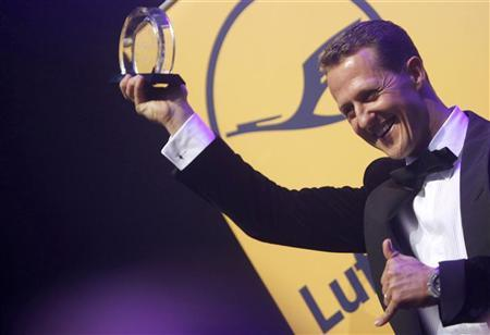 German Formula One driver Michael Schumacher poses with the Legend of Sport trophy at the German Sports Press Ball in Frankfurt November 10, 2012. REUTERS/Lisi Niesner