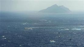 An aerial view shows a Japan Coast Guard patrol ship, fishing boats from Taiwan and Taiwan's Coast Guard vessel sailing side by side near Uotsuri island (top), a part of the disputed islands in the East China Sea, known as Senkaku in Japan, Diaoyu in China and Tiaoyutai in Taiwan, in this photo taken by Kyodo September 25, 2012. REUTERS/Kyodo