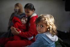 Семья палестинских беженцев, укрывшаяся в управляемой ООН школе в Газе 20 ноября 2012 года. Дипломатические усилия мировых лидеров по урегулированию конфликта между Израилем и палестинцами в секторе Газа усиливаются, но пока не могут остановить обмен ракетными ударами, общее число жертв которых за неделю уже превысило 100 человек. REUTERS/Ahmed Jadallah