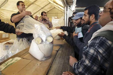 Palestinians wait to receive food supplies from the United Nations Relief and Works Agency (UNRWA) headquarters in Rafah in the southern Gaza Strip November 20, 2012. REUTERS/Ibraheem Abu Mustafa