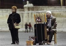 Un pensionato italiano a basso reddito canta pr strada con la moglie accanto. Roma, 9 dicembre, 2011. REUTERS/Alessandro Bianchi