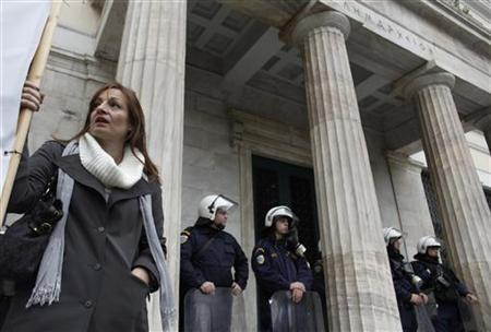 A municipality worker stands in front of riot police during a rally against state sector layoffs demanded by the country's international lenders, outside the city hall in Athens November 19, 2012. REUTERS/John Kolesidis (GREECE - Tags: CIVIL UNREST POLITICS BUSINESS EMPLOYMENT)