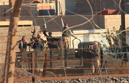 Free Syrian Army fighters hold up their weapons in the Syrian town of Ras al-Ain, as seen from the Turkish border town of Ceylanpinar, Sanliurfa province November 14, 2012. REUTERS/Stringer