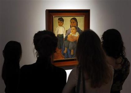 People look at the ''Madre e Hijos'' (Mother and Children) by Mexican master Diego Rivera during a preview of Latin American art at Christie's Auction house in New York November 19, 2012. The 1926 painting, expected to fetch $800,000, depicts a barefoot boy standing next to his sister, who is ensconced in their mother's lap. The children show a gravitas beyond their years. REUTERS/Brendan McDermid
