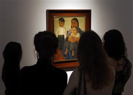 People look at the 'Madre e Hijos' (Mother and Children) by Mexican master Diego Rivera during a preview of Latin American art at Christie's Auction house in New York November 19, 2012. The 1926 painting, expected to fetch $800,000, depicts a barefoot boy standing next to his sister, who is ensconced in their mother's lap. The children show a gravitas beyond their years. REUTERS/Brendan McDermid