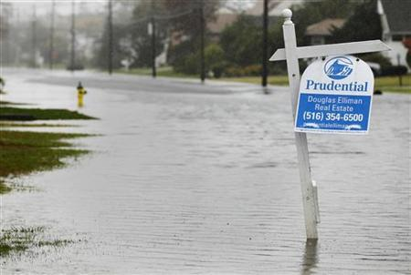 A for sale sign is seen along a flooded street in Freeport, New York October 29, 2012. REUTERS/Shannon Stapleton