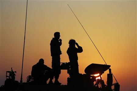 Israeli soldiers stand atop a mobile artillery unit positioned outside the northern Gaza Strip November 20, 2012. REUTERS/Darren Whiteside