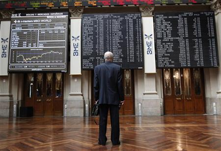 A trader looks at electronic boards at the stock exchange in Madrid June 12, 2012. REUTERS/Andrea Comas