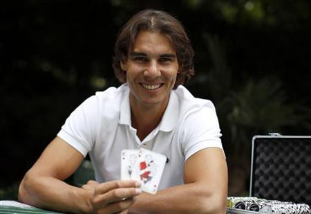 Spanish tennis player Rafael Nadal poses with playing cards depicting some of his 11 Grand Slam victories after an interview with Reuters in Madrid, September 18, 2012. REUTERS/Paul Hanna/Files