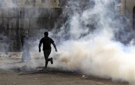 A protester runs with a tear gas canister, which was earlier fired by riot police, during a protest to mark the one-year anniversary of fatal clashes on Mohamed Mahmoud Street, near the Interior Ministry in Cairo November 20, 2012. REUTERS/Mohamed Abd El Ghany