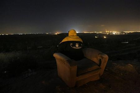 A private Israeli security guard sits on an armchair as he watches the fighting from a hill outside the northern Gaza Strip November 20, 2012. REUTERS/Yannis Behrakis