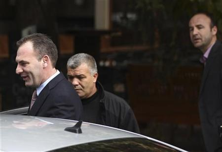 Fatmir Limaj (L), a prominent politician and a close ally of Prime Minister Hashim Thaci, walks towards a car in Pristina November 11, 2011. REUTERS/Hazir Reka