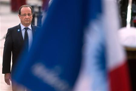 France's President Francois Hollande pays respect to the French flag as he attends a ceremony to commemorate the end of the World War One at the Arc de Triomphe in Paris, November 11, 2012. REUTERS/Bertrand Langlois/Pool