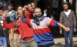 Manifestantes atiram pedras na tropa de choque durante um protesto para marcar um ano de embates fatais na rua Mohamed Mahmoud, próximo ao Ministério do Interior em Cairo, no Egito. 20/11/2012 REUTERS/Mohamed Abd El Ghany