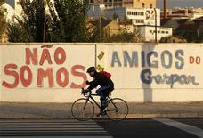 """Um ciclista pedala em frente a um grafitti sobre o ministro das Finanças de Portugal, Vitor Gaspar, nas ruas de Lisboa. O FMI disse que o país fez """"progressos consideráveis"""" em termos econômicos, mas o sucesso de seu plano depende das autoridades europeias. 16/10/2012 REUTERS/Hugo Correia"""