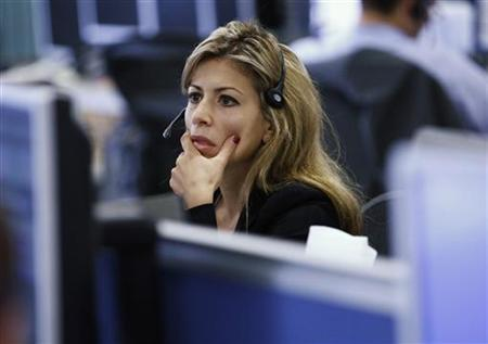 A worker on IG Index's trading floor looks at her computer screens in London September 22, 2011. REUTERS/Andrew Winning/Files