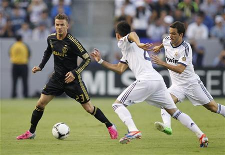 Los Angeles Galaxy's David Beckham (L) controls the ball as Real Madrid's Jose Maria Callejon (C) and Gonzalo Higuain (R) defend during the first half of their World Football Challenge international friendly soccer match in Carson, California August 2, 2012. REUTERS/Danny Moloshok