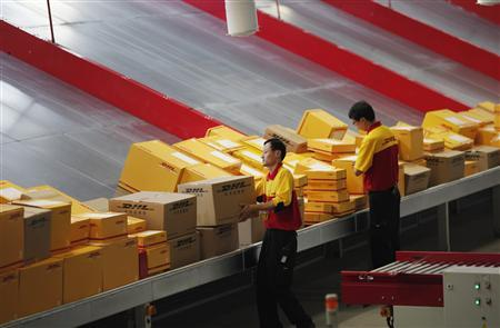 An employee carries a box at a workstation during an operational test of the new DHL North Asia Hub in Shanghai in this July 12, 2012 file photo. REUTERS/Carlos Barria/Files