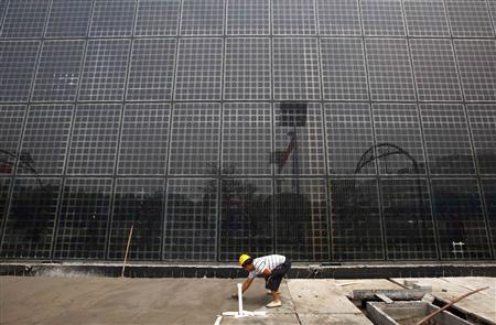 A worker smoothes out cement in front of a building covered in solar panels near the factory of Yingli Green Energy Holding Company, also known as Yingli Solar, in the city of Baoding, Hebei Province in this June 20, 2011 file photo. REUTERS/David Gray/Files