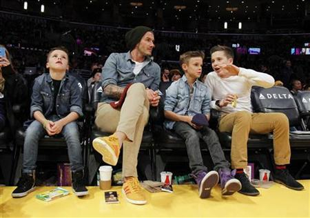 British soccer player David Beckham (2nd L) sits courtside with his sons Cruz (L), Romeo (2nd R) and Brooklyn (R) during the NBA basketball game between the Los Angeles Lakers and Phoenix Suns in Los Angeles November 16, 2012. REUTERS/Danny Moloshok