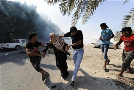 Anti-government protesters run from tear gas fired by riot police, as they attempt to get to the village of Diraz, west of Manama November 9, 2012. REUTERS/Stringer