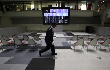 A security guard walks past in front of a screen displayed market indices from around the world at the Tokyo Stock Exchange in Tokyo November 5, 2012. REUTERS/Issei Kato