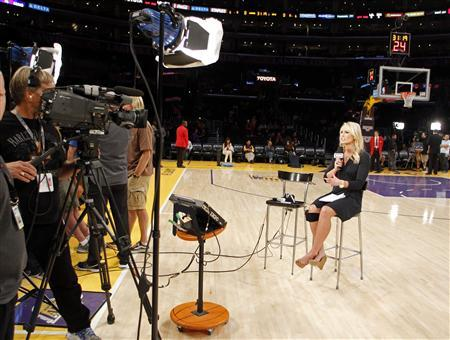 YES Network sports reporter Sarah Kustok talks on the court before the Los Angeles Lakers play against the Brooklyn Nets in a NBA basketball game in Los Angeles November 20, 2012. News Corp will acquire a 49 percent equity stake in the YES Network from the New York Yankees baseball club and its partners, giving the media company a major sports presence in the largest U.S. TV market. REUTERS/Danny Moloshok