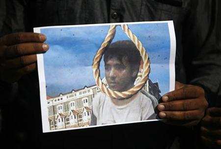 A man holds a picture of Mohammad Ajmal Kasab with a noose, as he celebrates Kasab's execution, in Ahmedabad November 21, 2012. REUTERS/Amit Dave