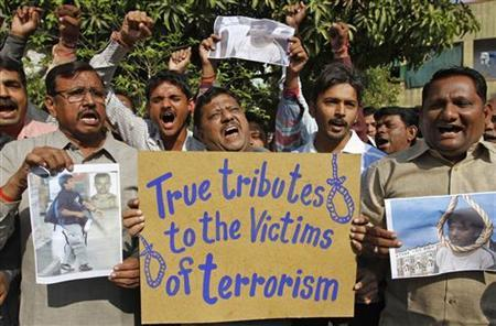 People hold a placard and pictures of Mohammad Ajmal Kasab, as they celebrate in Ahmedabad November 21, 2012. REUTERS/Amit Dave