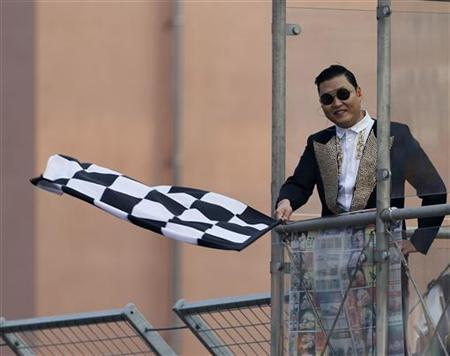 South Korea singer Psy waves the chequered flag to Formula One drivers finishing the South Korean F1 Grand Prix at the Korea International Circuit in Yeongam October 14, 2012. REUTERS/Bazuki Muhammad/Files