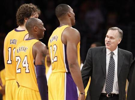 Los Angeles Lakers head coach Mike D'Antoni (R) smiles with Pau Gasol (L) of Spain, Kobe Bryant (2nd L) and Dwight Howard during the second half of their NBA basketball game against the Brooklyn Nets, as he makes his game coaching debut for the Lakers in Los Angeles November 20, 2012. REUTERS/Danny Moloshok