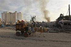 Los ataques aéreos israelíes sacudieron la Franja de Gaza y cohetes palestinos atravesaron la frontera en momentos en que la secretaria de Estado estadounidense, Hillary Clinton, se reunía en Jerusalén en las primeras horas del miércoles, en busca de una tregua que pueda detener una incursión terrestre en el enclave costero. En la imagen, un hombre pasa con su burro frente a unas oficinas del gobierno destruidas tras lo que según testigos fue un ataque aéreo israelí en Gaza, el 21 de noviembre de 2012. REUTERS/Mohammed Salem