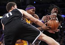 Los Angeles Lakers' Dwight Howard (C) attempts to grab a defensive rebound between Brooklyn Nets' Brook Lopez (L) and Gerald Wallace (R) during the first half of their NBA basketball game in Los Angeles November 20, 2012. REUTERS/Danny Moloshok