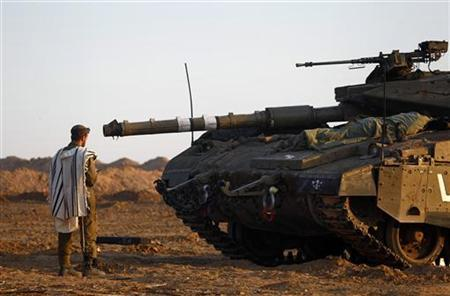 An Israeli soldier prays by a tank at an Israeli Defence Forces (IDF) staging area in the central Gaza border November 21, 2012. Israeli air strikes shook the Gaza Strip and Palestinian rockets struck across the border as U.S. Secretary of State Hillary Clinton held talks in Jerusalem in the early hours of Wednesday, seeking a truce that can hold back Israel's ground troops. REUTERS/Yannis Behrakis (ISRAEL - Tags: CONFLICT CIVIL UNREST MILITARY RELIGION)