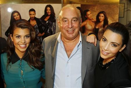 Kourtney (L) and Kim Kardashian pose with Arcadia Group chief executive Philip Green (C) during a media event before the launch of their clothing line Kardashian Kollection at the British high street retail chain Dorothy Perkins in London November 7, 2012. REUTERS/Chris Helgren