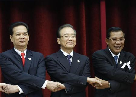 Chinese Premier Wen Jiabao (C) poses during the family photo at the 15th ASEAN-China summit meeting at the Peace Palace in Phnom Penh, November 19, 2012. Also in the picture are Vietnam's Prime Minister Nguyen Tan Dung (L) and Cambodia's Prime Minister Hun Sen. REUTERS/ Samrang Pring