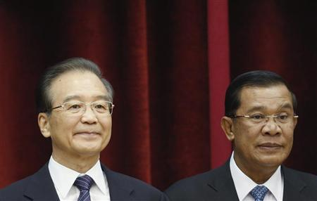 Chinese Premier Wen Jiabao (L) poses during the family photo at the 15th ASEAN-China summit meeting at the Peace Palace in Phnom Penh, November 19, 2012. Also in the picture is Cambodia's Prime Minister Hun Sen. REUTERS/ Samrang Pring