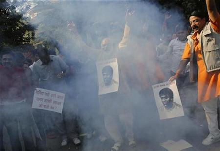 Supporters of the hardline Hindu group Bajrang Dal, dance while wearing pictures of Mohammad Ajmal Kasab, amid smoke caused by fire crackers during the celebrations in New Delhi November 21, 2012. REUTERS/Adnan Abidi