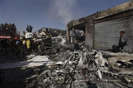 Firefighters work to extinguish a fire after a plane crashed in Sanaa November 21, 2012. REUTERS/Mohamed al-Sayaghi