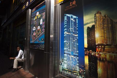 A man sits in front of a real estate agency displaying advertisements of residential development near the West Kowloon luxurious apartment district in Hong Kong October 31, 2012. REUTERS/Tyrone Siu