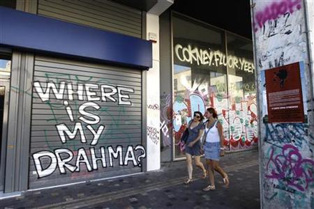 Two women walk past by a shutter of a closed bank with a graffiti in central Athens, August 28, 2012. REUTERS/John Kolesidis