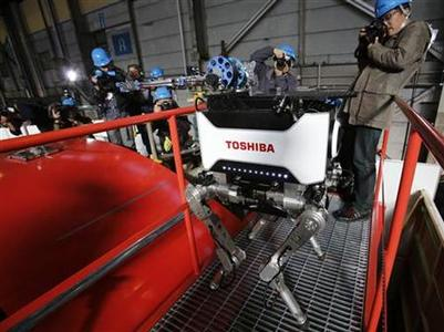 Photographers take photos of Toshiba Corp's new four-legged robot which the company says is capable of carrying out investigative and recovery work at tsunami-crippled Fukushima Daiichi nuclear power plant during a demonstration at the company's Yokohama complex in Yokohama, south of Tokyo November 21, 2012. REUTERS/Yuriko Nakao